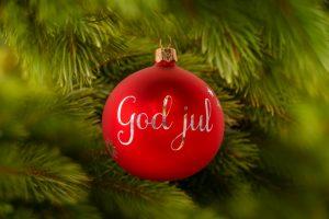 """Röd julkula med silvrig svensk text """"god jul"""" hängde i julgranen."""